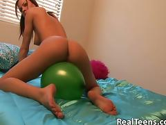 Sexy teen with perky natural tits riding a balloon on her bed